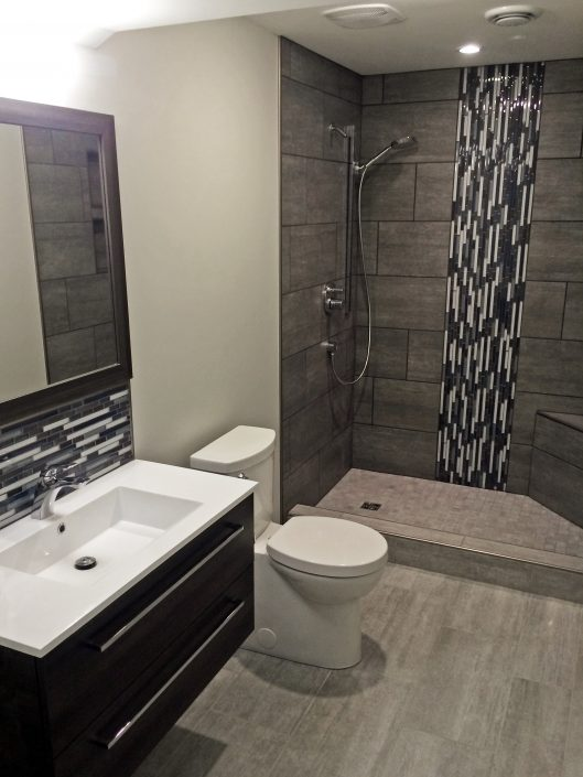 New basement bathroom with IKEA® cabinets (great value!) and custom tile work including radiant floor heating.