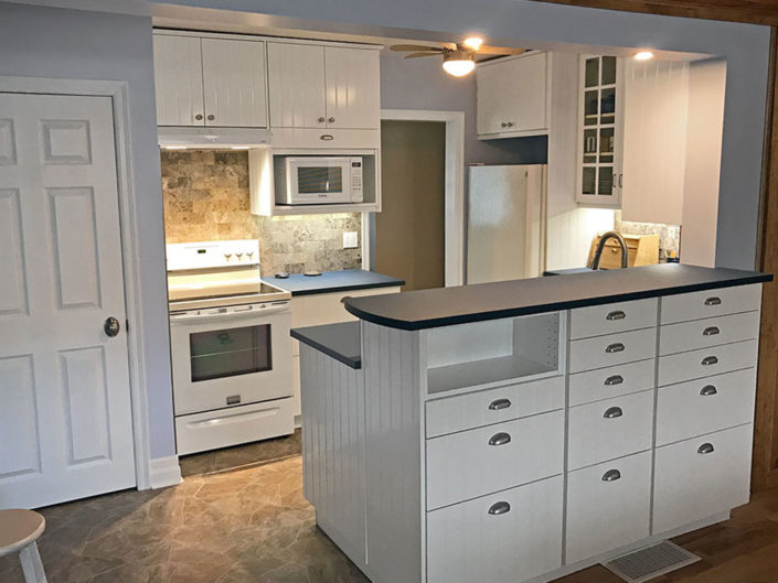From 50's bungalow kitchen with added tile and counter tops of the years, to IKEA Paperstone counter top, under counter stainless steel sink, Europa Travertine, grey honed 3x6 tile backsplash & under cabinet strip lighting.