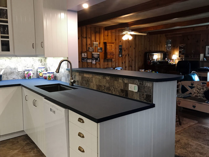 IKEA cabinets Paperstone counter top with under counter mounted stainless steel sink, Europa Travertine, grey honed 3x6 tile backsplash and under cabinet low voltage strip lighting.